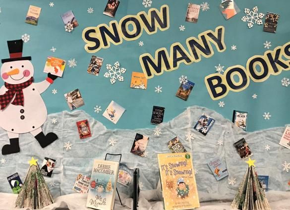 """A holiday book display that reads """"snow many books"""" at  Charlotte Mecklenburg Library's Mint Hill Library."""