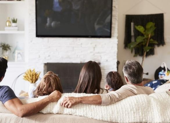 A family watches TV together.