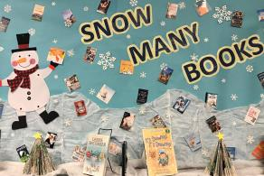 "A holiday book display that reads ""snow many books"" at  Charlotte Mecklenburg Library's Mint Hill Library."