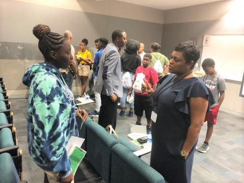 "A Charlotte Mecklenburg student engages in conversation with a careerwoman during the Library's ""Bigger than High School"" event in July, 2019."